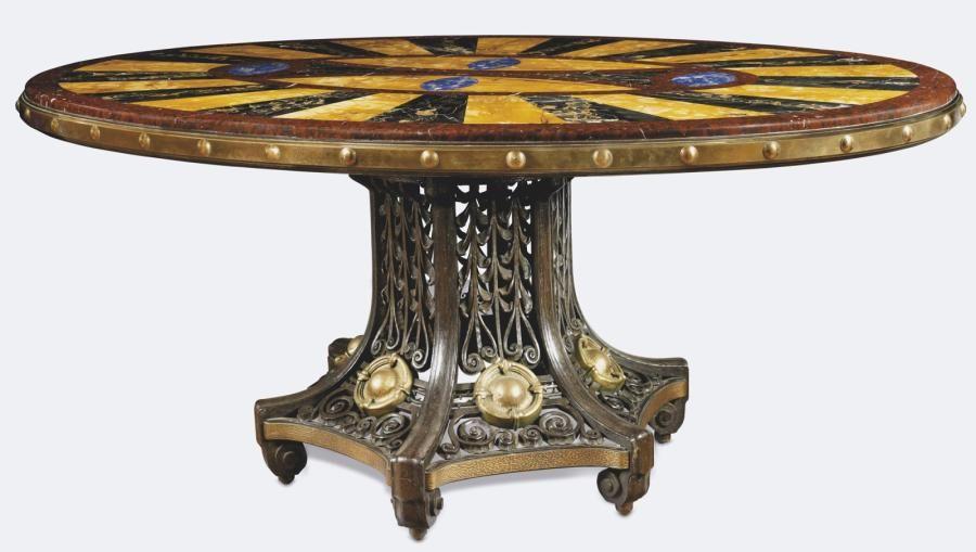 EDGAR BRANDT (1880-1960)  EXCEPTIONNELLE TABLE de milieu en fer forgé. Le plateau ovale, ceinturé de bronze est constitué d'une marqueterie de marbres et pierres de couleur, à décor rayonnant. Il est supporté par un important fût central hexagonal et ajouré, orné de cabochons de bronze et s'évasant largement vers la base. Piétement se terminant en volutes. Circa 1920 H 76,5, L 179, P 123,5cm