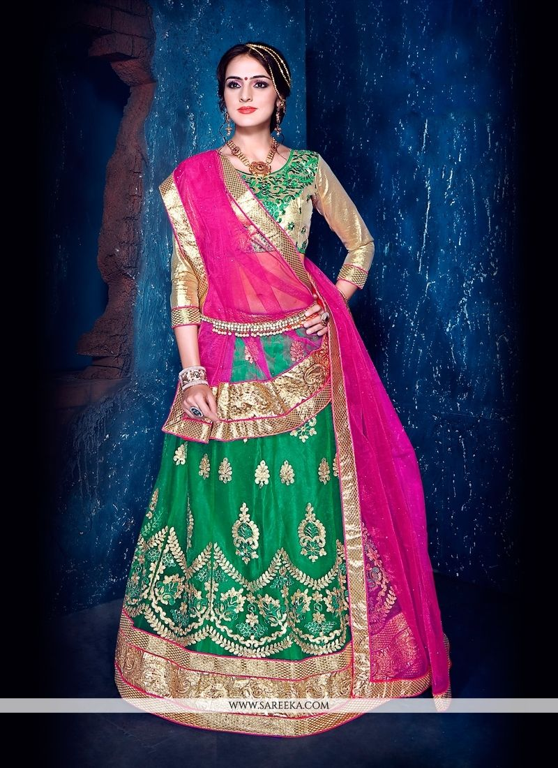 Give in to the exotic confluence of today and tomorrow in this beautiful attire. You are sure to make a strong fashion statement with this green net and satin a line lehenga cholicomes with matching c...
