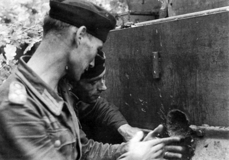 Commander of Tiger IV tank 323 from 3rd company 503rd heavy tank battalion, unter-offizier Futermeister is showing the cavity left by a Soviet shell on the armour of his tank. Kursk salient, 1943.