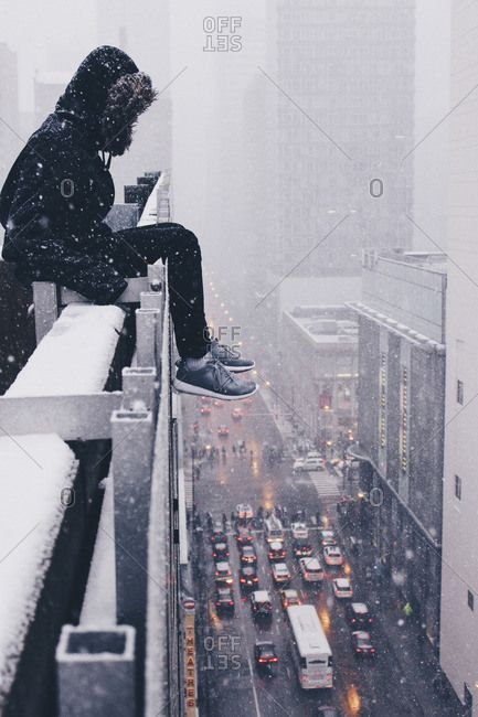 Person Sitting On The Ledge Of A Skyscraper In Chicago Illinois Winter Snow