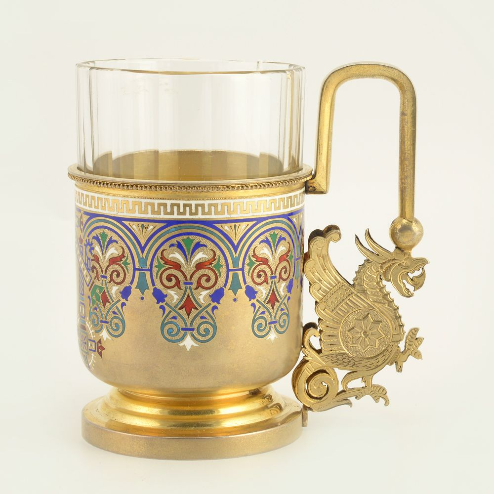 "A Russian silver gilt and champleve enamel tea glass holder, Ivan Khlebnikov, St Petersburg, 1896. The body decorated with an enameled Russian ""dacha"" or traditional peasant house; the surrounding border of stylized multi-color scrolling floral and foliate motifs in champleve enamel. The handle decorated with a gilded silver figural griffon."