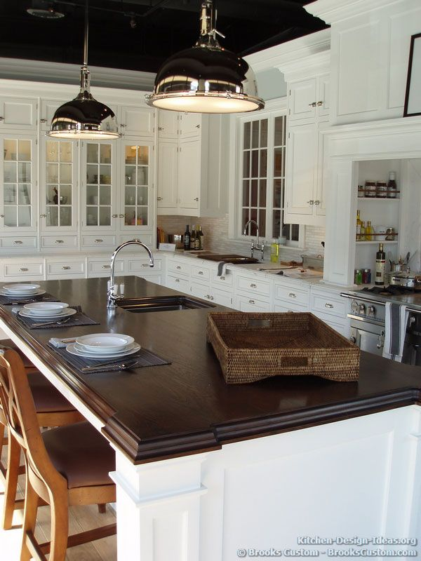 White Kitchens By Design traditional white kitchen with a walnut island countertop