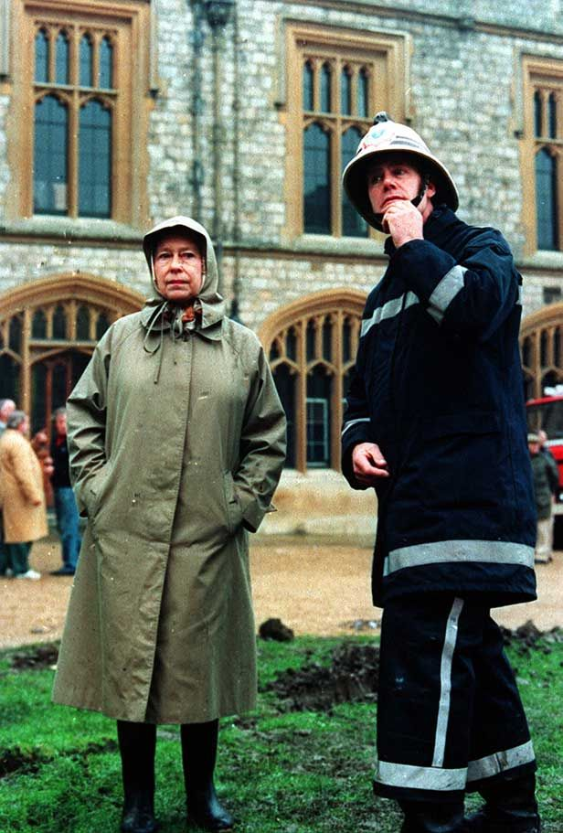 The Queen and a fireman inspect the damage to Windsor Castle