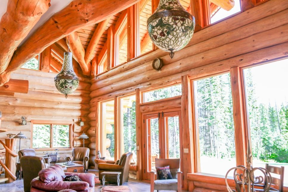 The tower house at the Huston Family Estate features a spacious, open living area with log walls and large windows boasting stunning views of the outdoors. Cozy leather armchairs fit perfectly with the rustic design aesthetic.