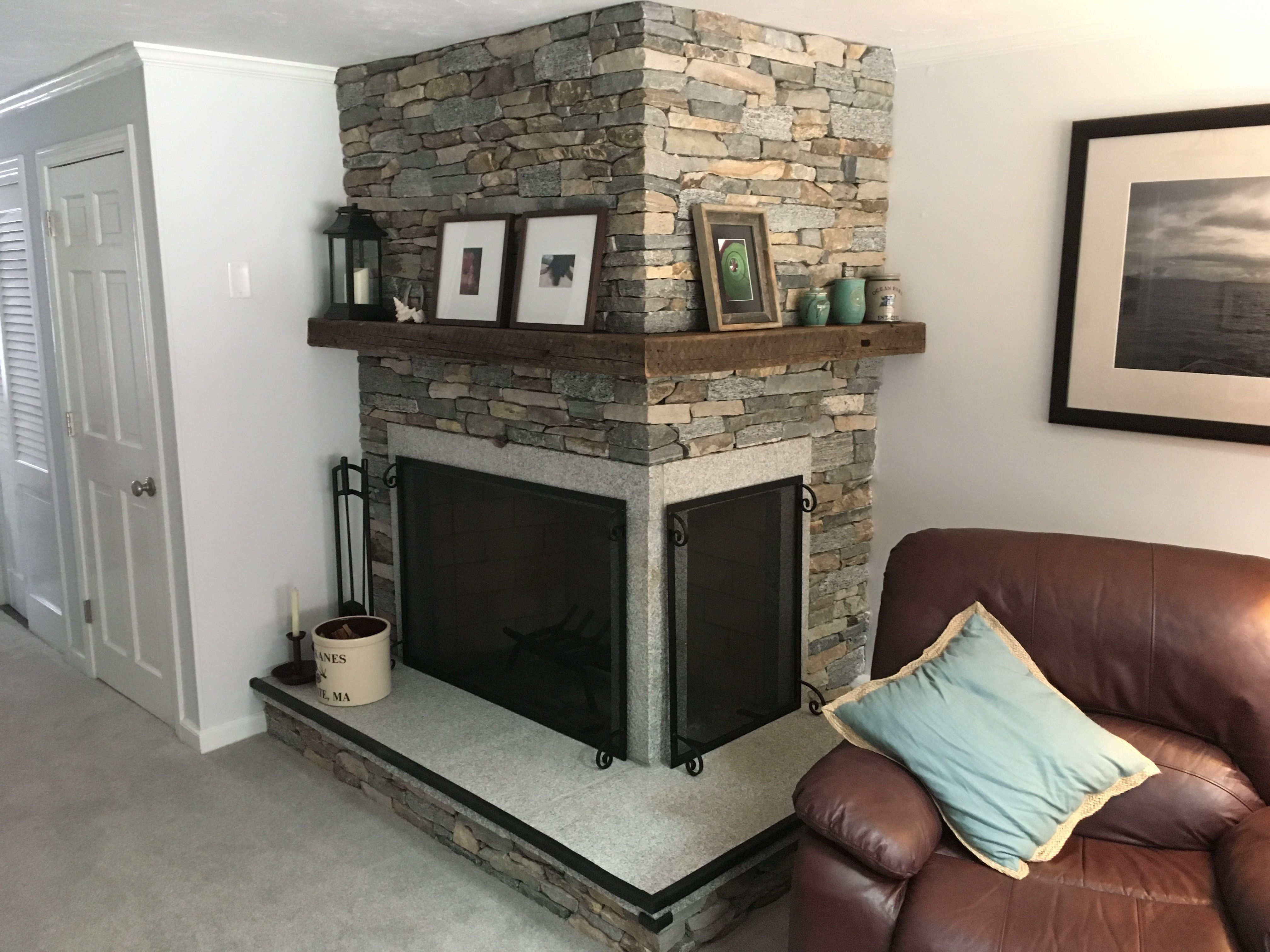natural stone corner fireplace with granite hearth
