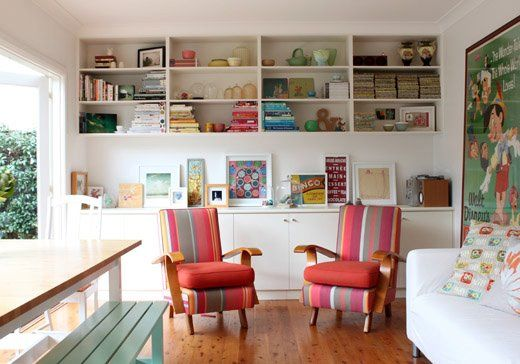 love the chairs recovered in stripey fabric, bookshelves and artwork