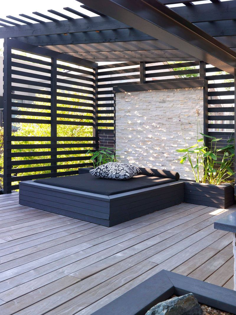 This Built In Outdoor Daybed With A Stone Wall And Planters Sits
