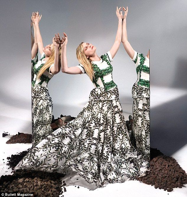 Glammed up: The blonde beauty wears an elegant printed gown as she poses in front of another mirror