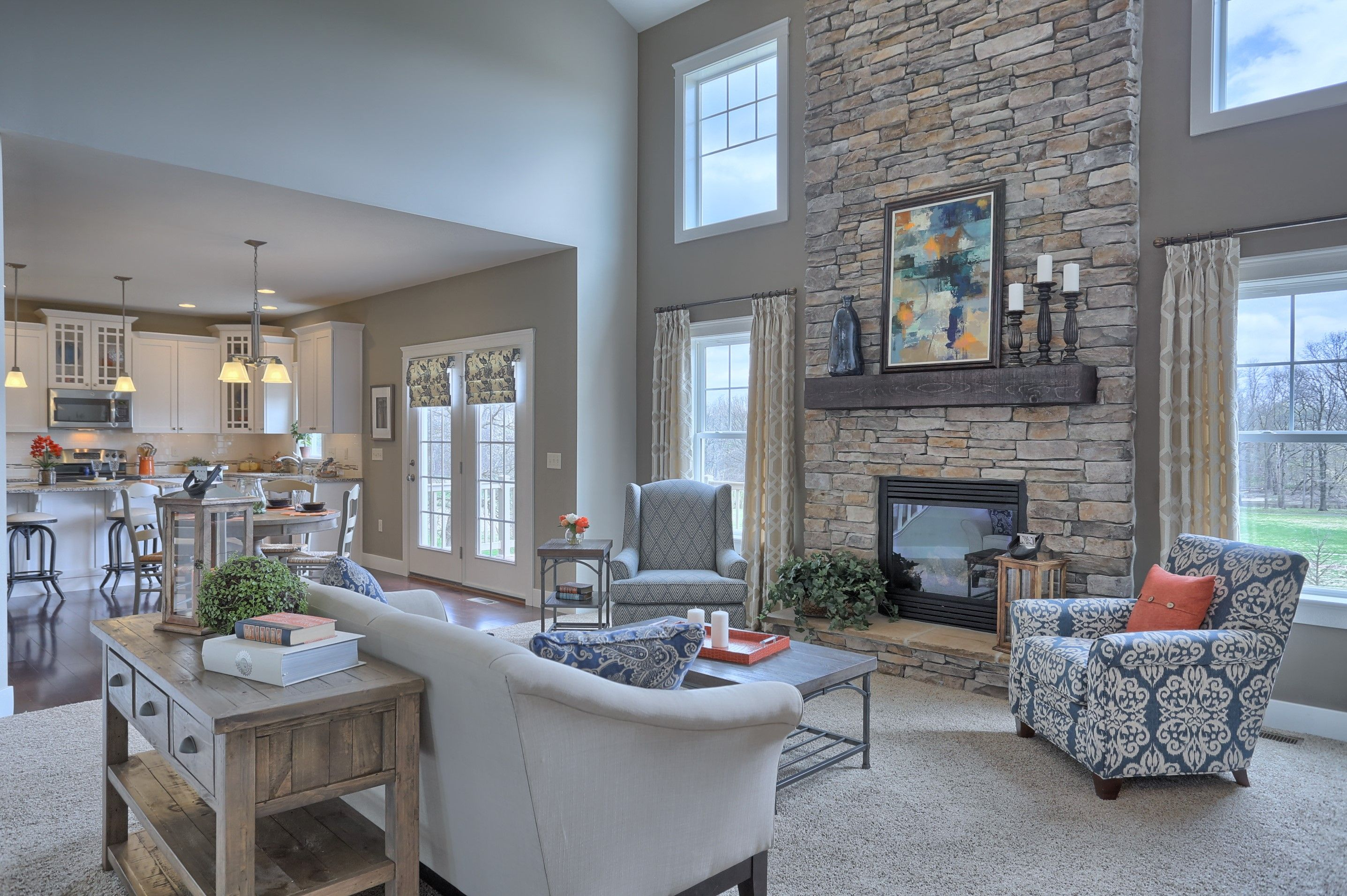 Great room with story ceiling gas fireplace with stone surround