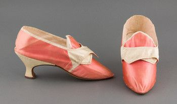 A pair of pink satin shoes with straps and a satin heel. Pointed tongue and toe. Straight side seam.