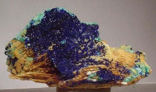 Azurite, Baryte  Locality: St Gertraudi, Brixlegg - Rattenberg, Brixlegg - Schwaz area, Inn valley, North Tyrol, Tyrol, Austria  4.2 x 2.3 x 1.9 cm. An excellent and showy Austrian combination specimen from a less well-known locality - St. Gertraudi, Tyrol. A rich field of very sparkly azurite microcrystals is aesthetically set on iron-stained, bladed barite and nicely complimented by a scattered bit of malachite.