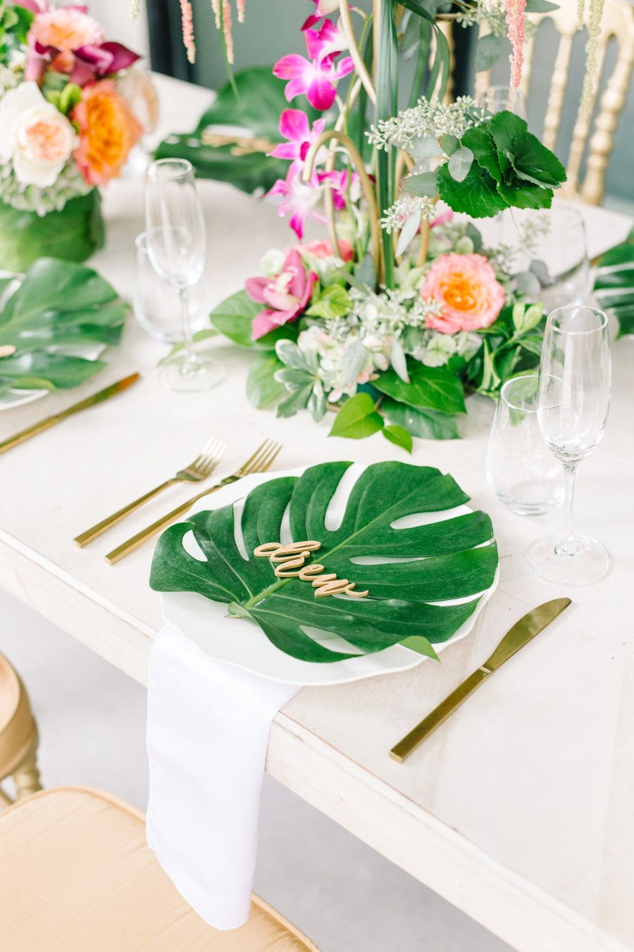 I Like The Plant In Center And Colors Palm Leaf Place Settings Tropical Centerpieces With Orchids Greens Arranged By Coastal Creations