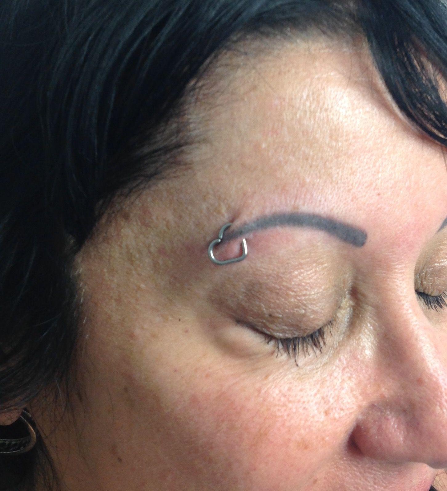 Healed Eyebrow Piercing With A Niobium Heart Eyebrow Bridge