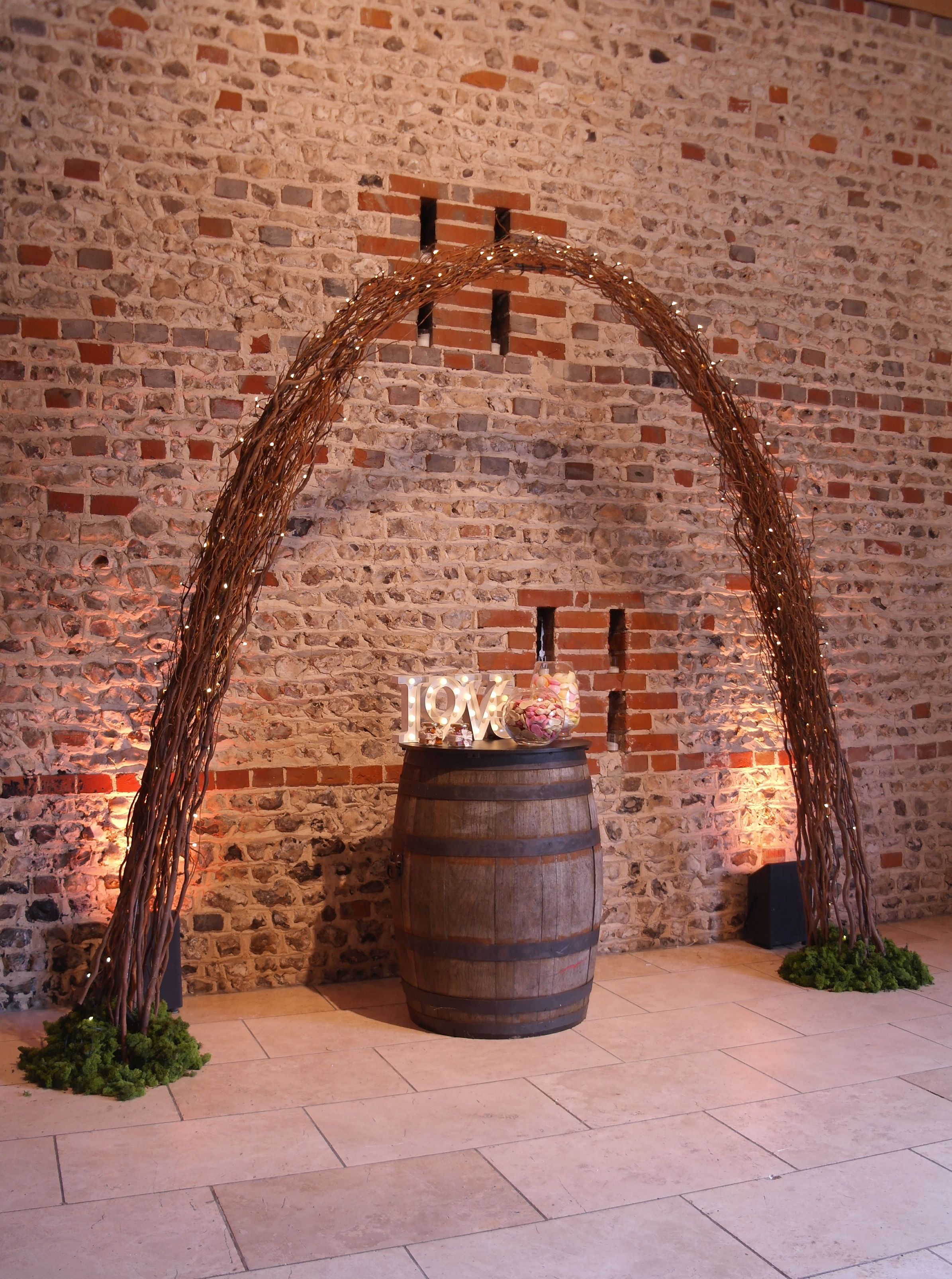 Twisted willow archway with pealights and barrel poseur table for a rustic barn wedding at Upwaltham Barns by www.stressfreehire.com #venuetransformers