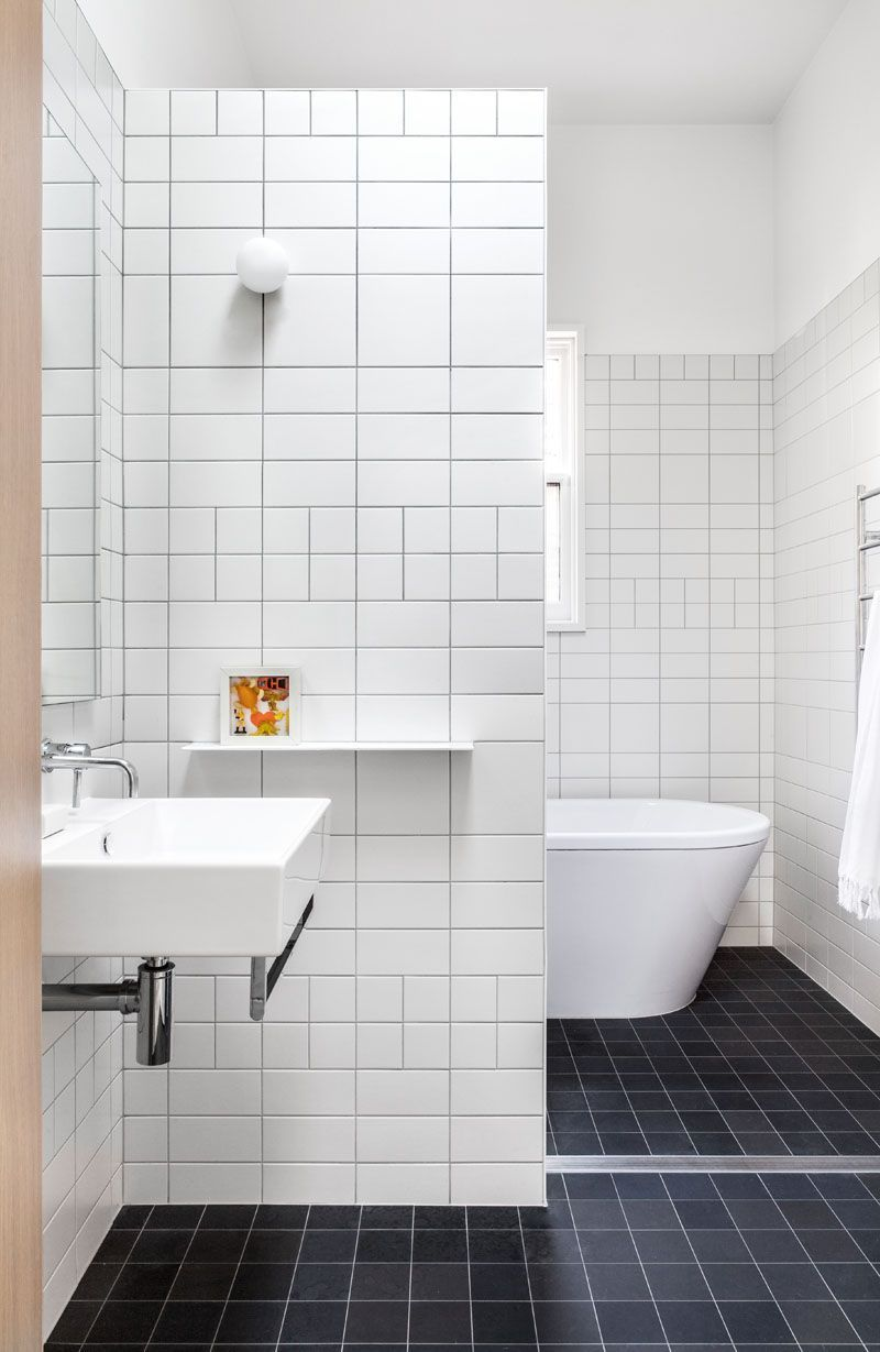 In this modern and simple bathroom, white tiles in different sizes ...