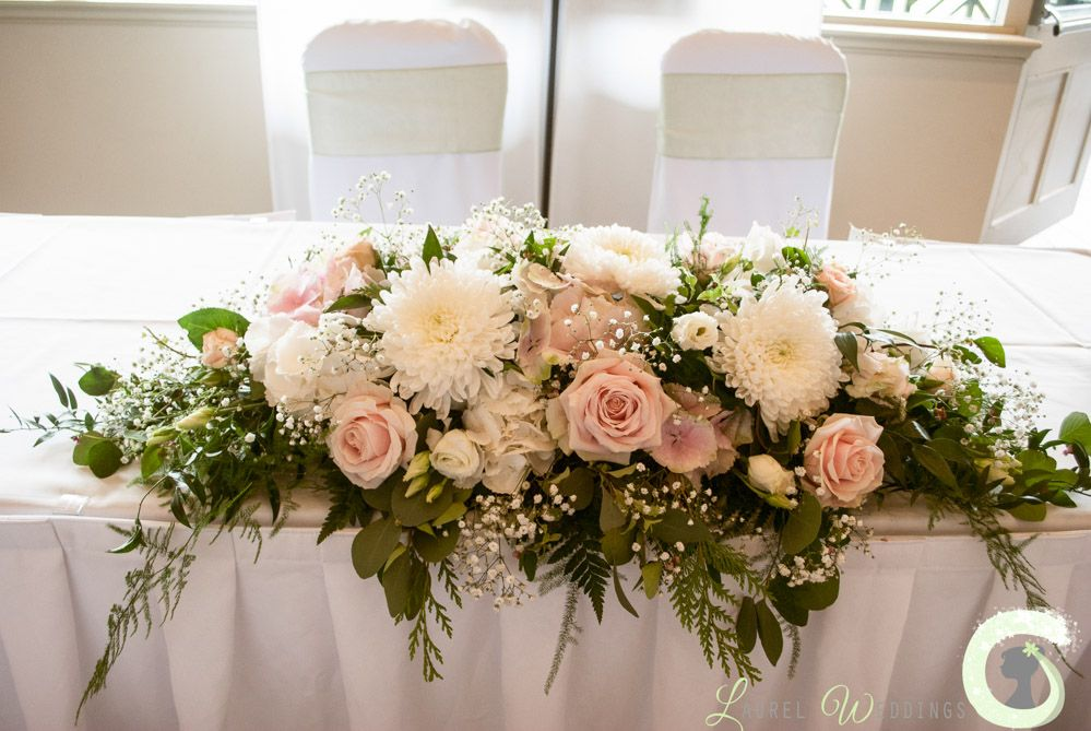 Blush pink and ivory ceremony table arrangement at the for Floral table decorations for weddings