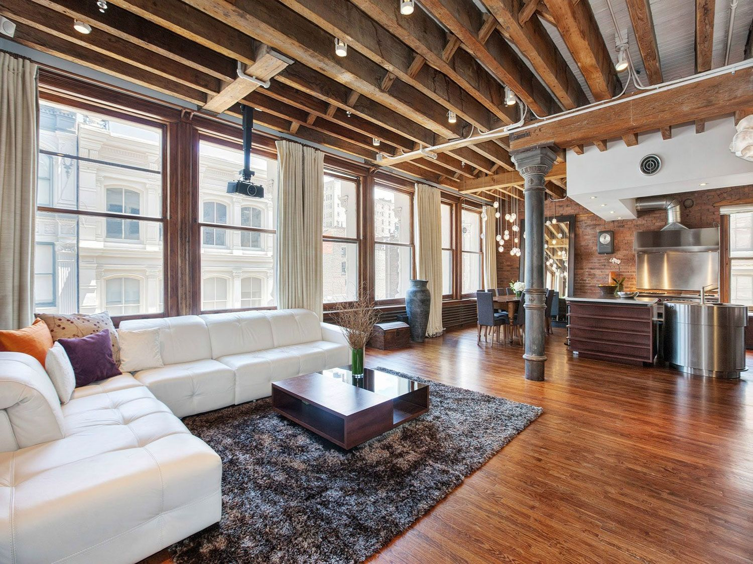 Open Plan Apartment With Exposed Wood Beams And Iron