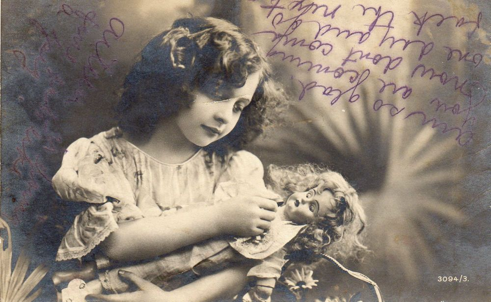 VINTAGE POSTCARD OF A LITTLE GIRL AND HER DOLL