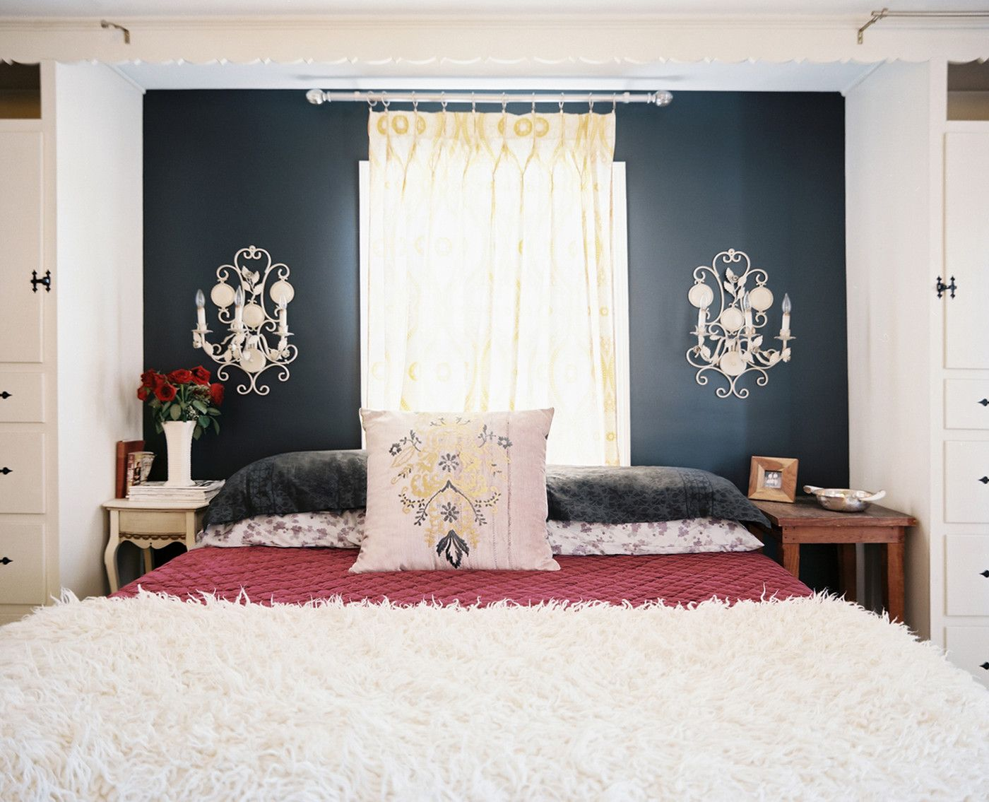 A black accent wall and white vintage sconces in a bedroom