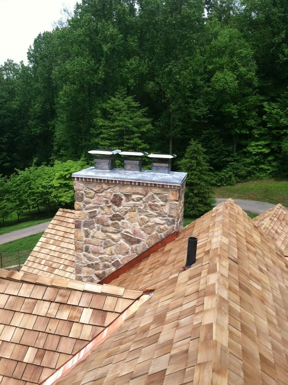 beautiful cedar roof stone chimney with a custom made lead