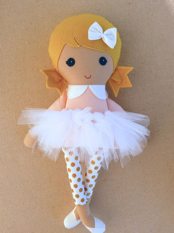 This is a handmade cloth doll measuring 20 inches. She is wearing a sweet, soft pink dress with white and gold