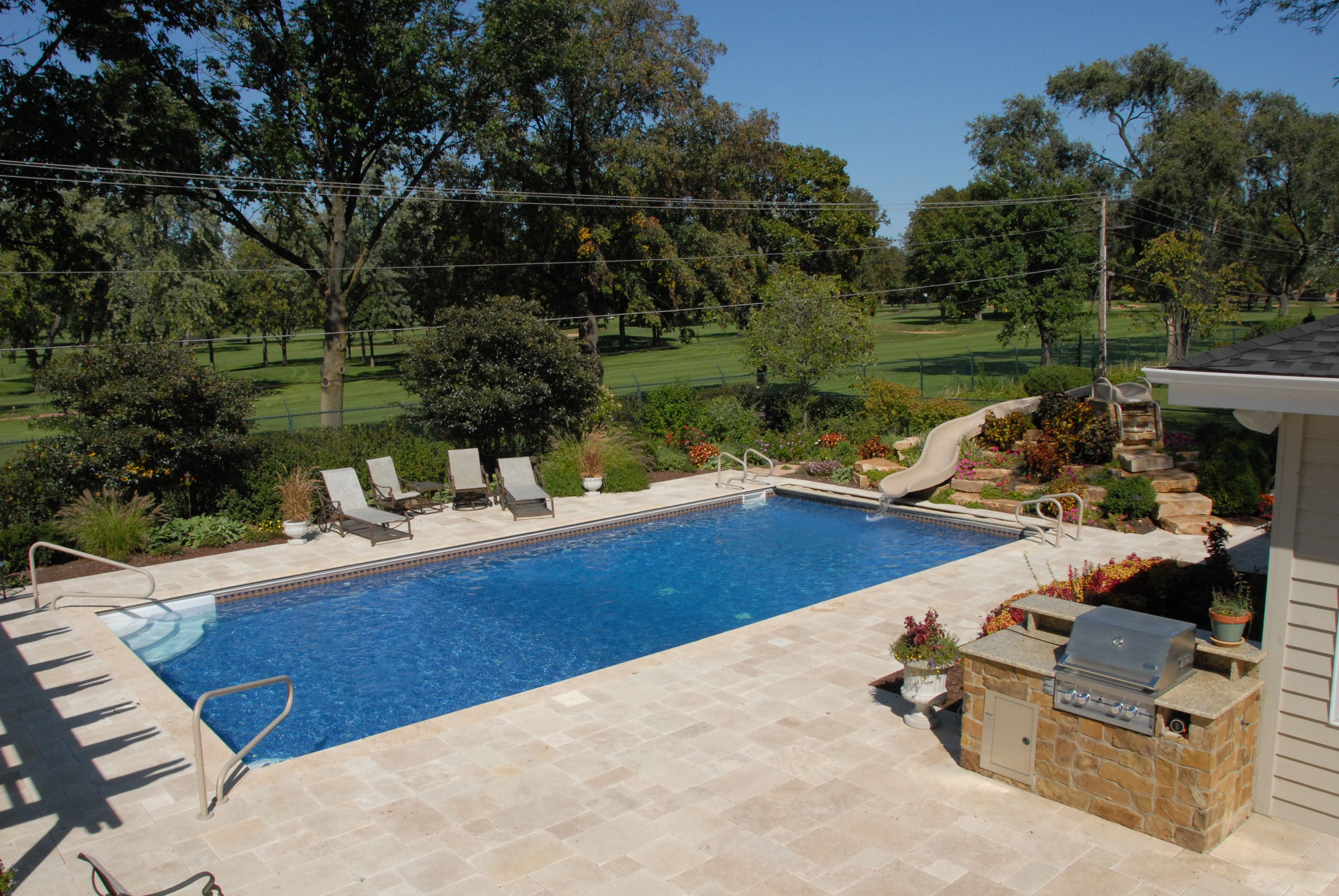 Vinyl Pool With A Custom Built Slide And Paver Brick Grill Area