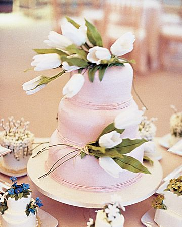 This cake has round layers, pink icing, and white sugar tulips.