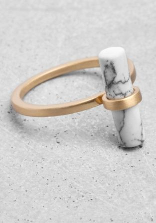 Made from brass, this elegant ring features a genuine stone bar with a marble-looking finish. Due to the nature of the stone, each piece has a unique appearance.