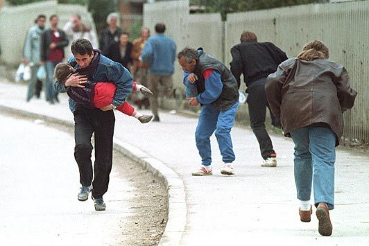 Dad protecting his child while under fire from a sniper during the Bosnian War.