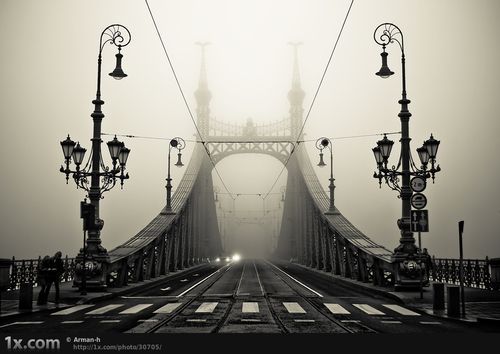 Black and white bridge surrounded by fog...