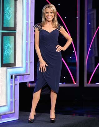 LA FEMME Navy stretch mesh cocktail dress w/crossover v-neckline, nude illusion & navy beaded lace shoulders & cap sleeves, diagonally pleated wrap skirt w/slit on right  | Vanna White's dresses | Wheel of Fortune