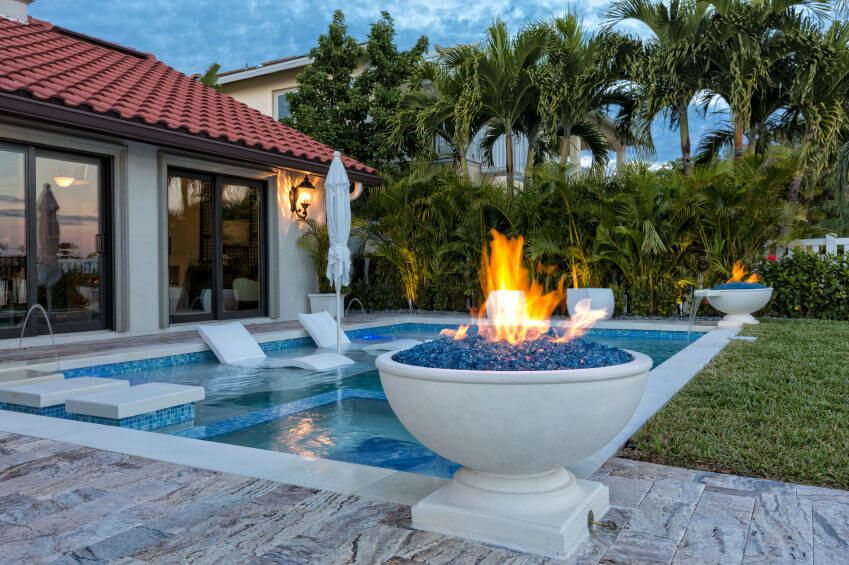 Pool With Gas Fuelled White Ornate Fire Bowls Placed In A Corner Of The On Edge Patio And Other Gr
