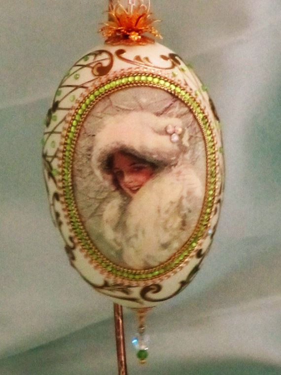 A unique ornament for your tree, as a gift, or to exchange, this egg is decorated with a vintage silk print. The giving of decorated eggs has been an important tradition in the Old World for many years. The egg, symbolizing the source of life, is given to express the love and friendship that lies deep in the heart of the giver.  Please note, this piece is made from a real unfertilized goose egg that has been emptied, cleaned, rinsed and sanitized before carving and decorating. It will be…