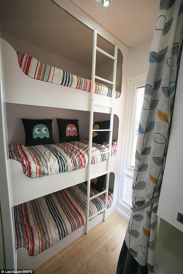 with fixed triple bunk beds on one end of the caravan and a sofa in the
