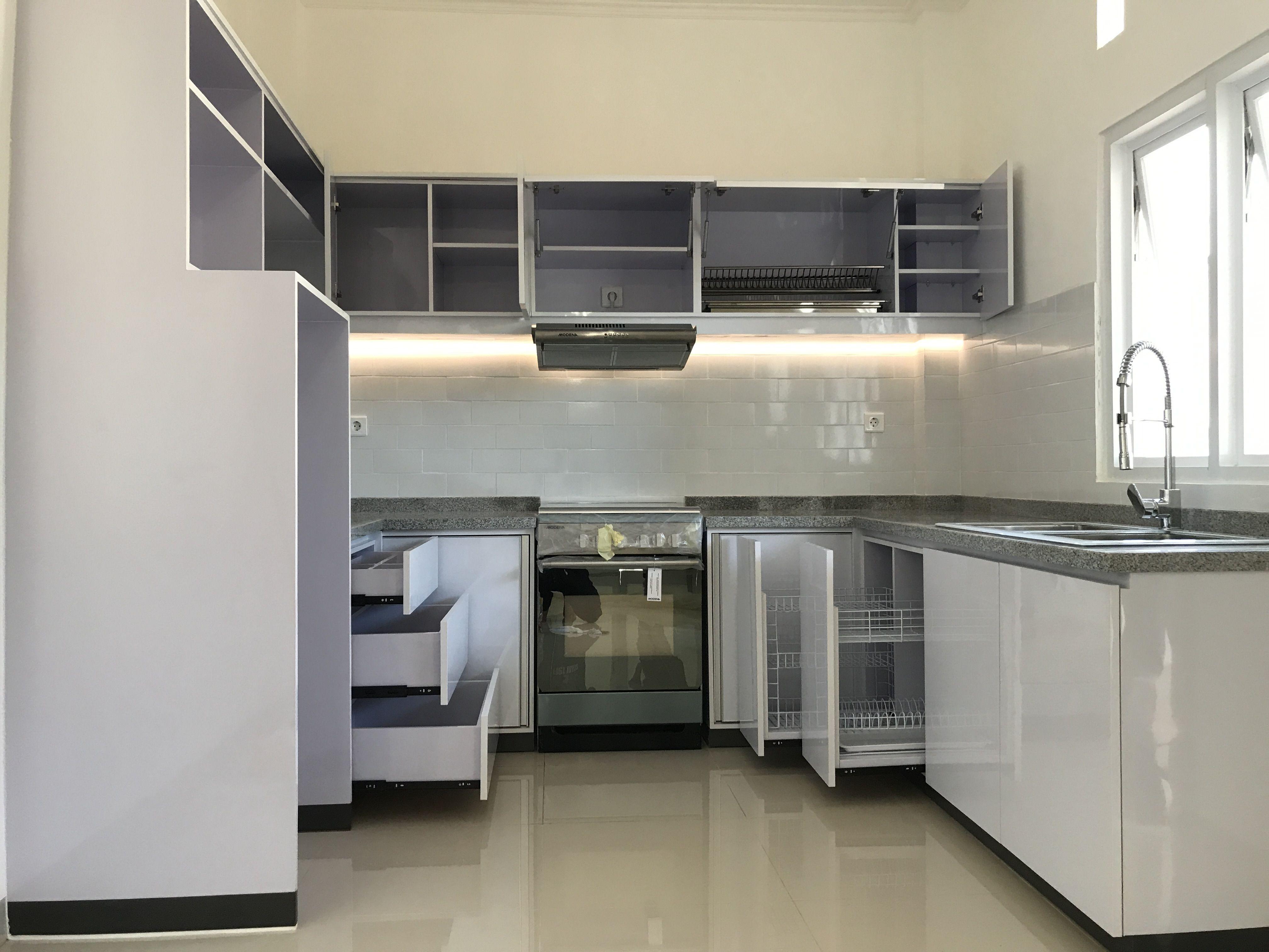 Kitchen set cantik ini dibalut hpl putih glossy dengan top table batu granit abu dan backsplash menggunakan subway tile