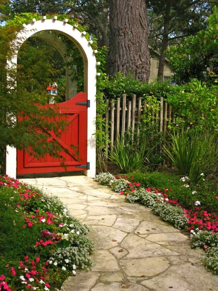Portão de madeira vermelho com arco branco e um belo jardim. http ...