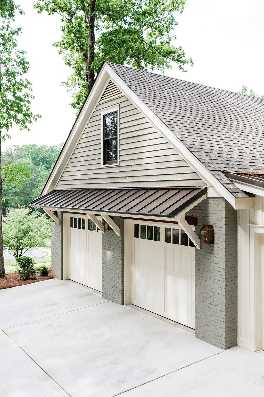 Sage Green Painted Brick Home With Separate Garage Awning Over The Garage Doors Lantern Sconces On Either Si House Awnings Garage Door Design Garage Design