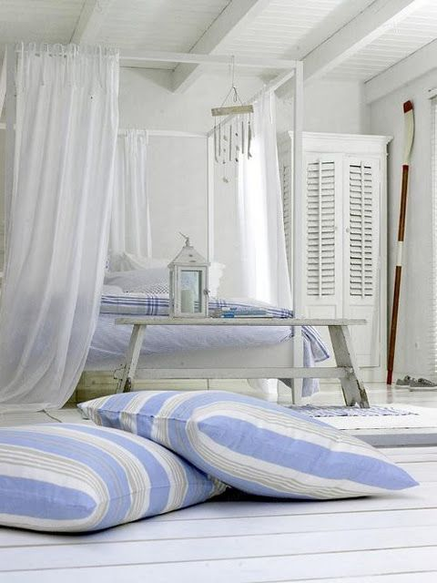 Sheers, white bed frame, louvered doors on armoir, blue and white cushions, oar, planks, layered blue and white scatter rugs <3