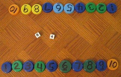 """Aquí tenemos otro juego de matemáticas con tapones de plástico para trabajar los amigos del 10 y por extensión el cálculo básico visto en """"Love2learn2day"""" descubierto vía""""El color de la escuela"""". Consiste en numerar los tapones y tirar dos dados (elegir la operación) e ir eliminando todos los tapones de …"""