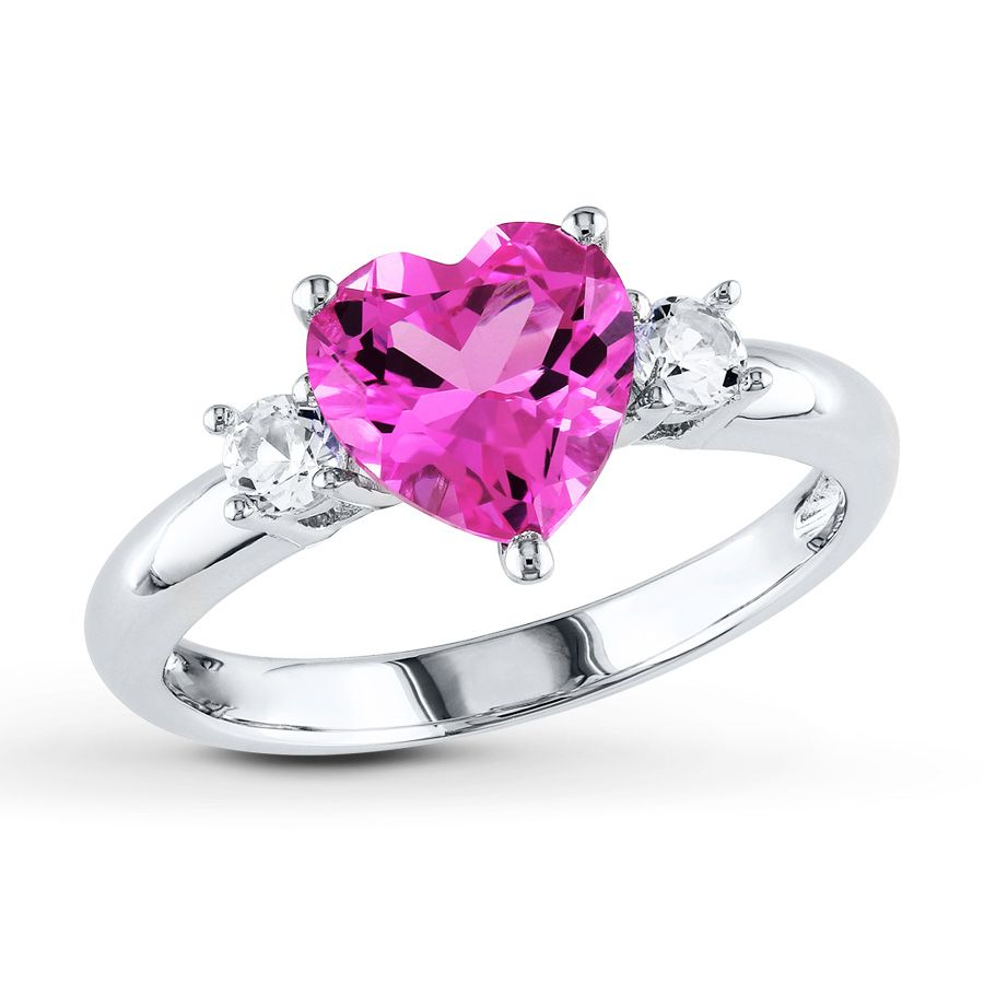 A center heart-shaped lab-created pink sapphire is enhanced with ...