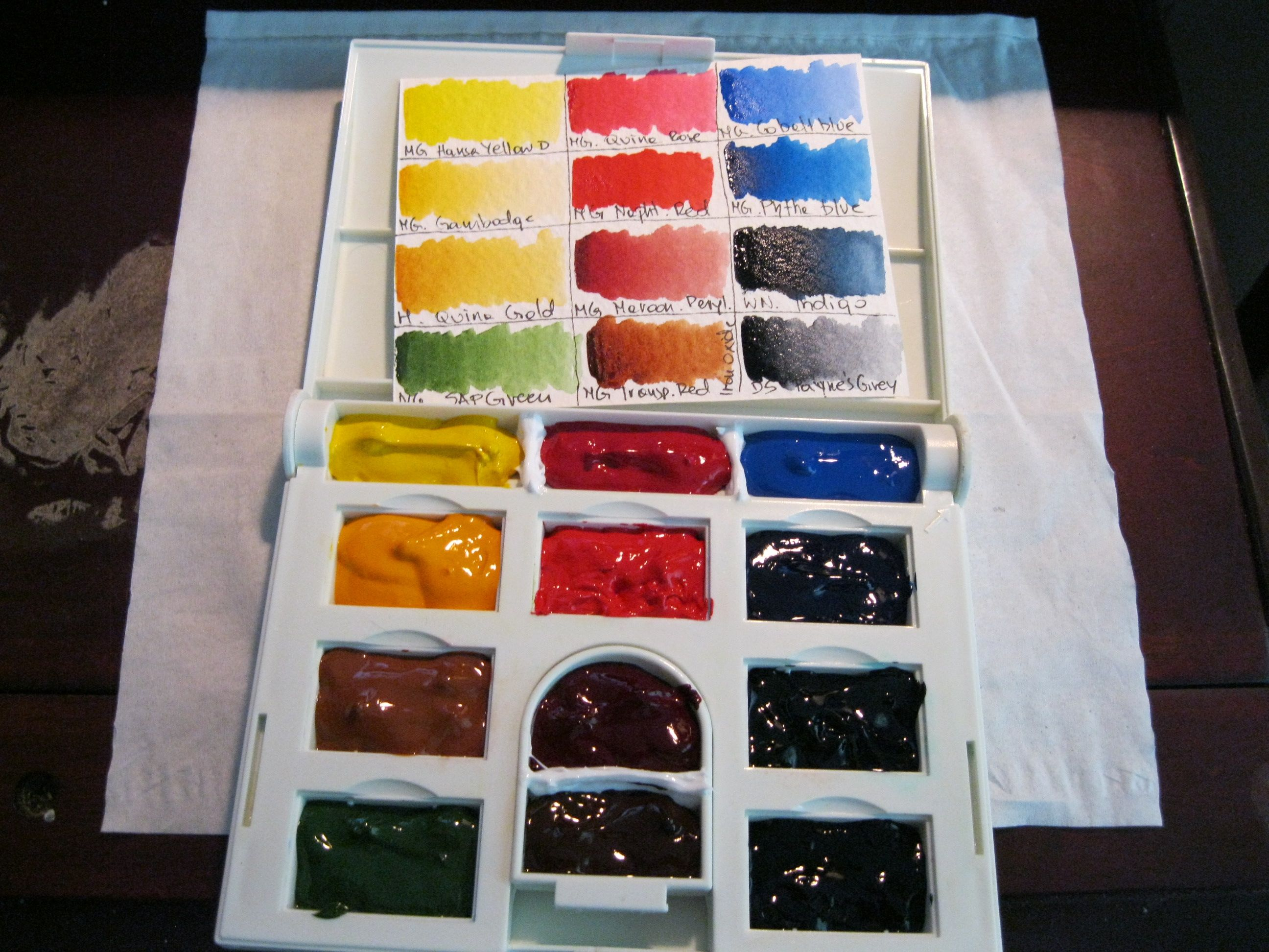 My modified Cotman travel palette. I used bathroom silicon to create extra wells.  It gives me 12 wells in total. I put M.Graham watercolors paint without pans.