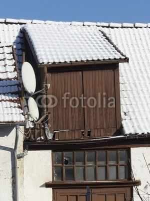 Schneebedeckte Scheune mit braunen Holztüren und Satellitenschüsseln in Großauheim am Main bei Hanau in Hessen