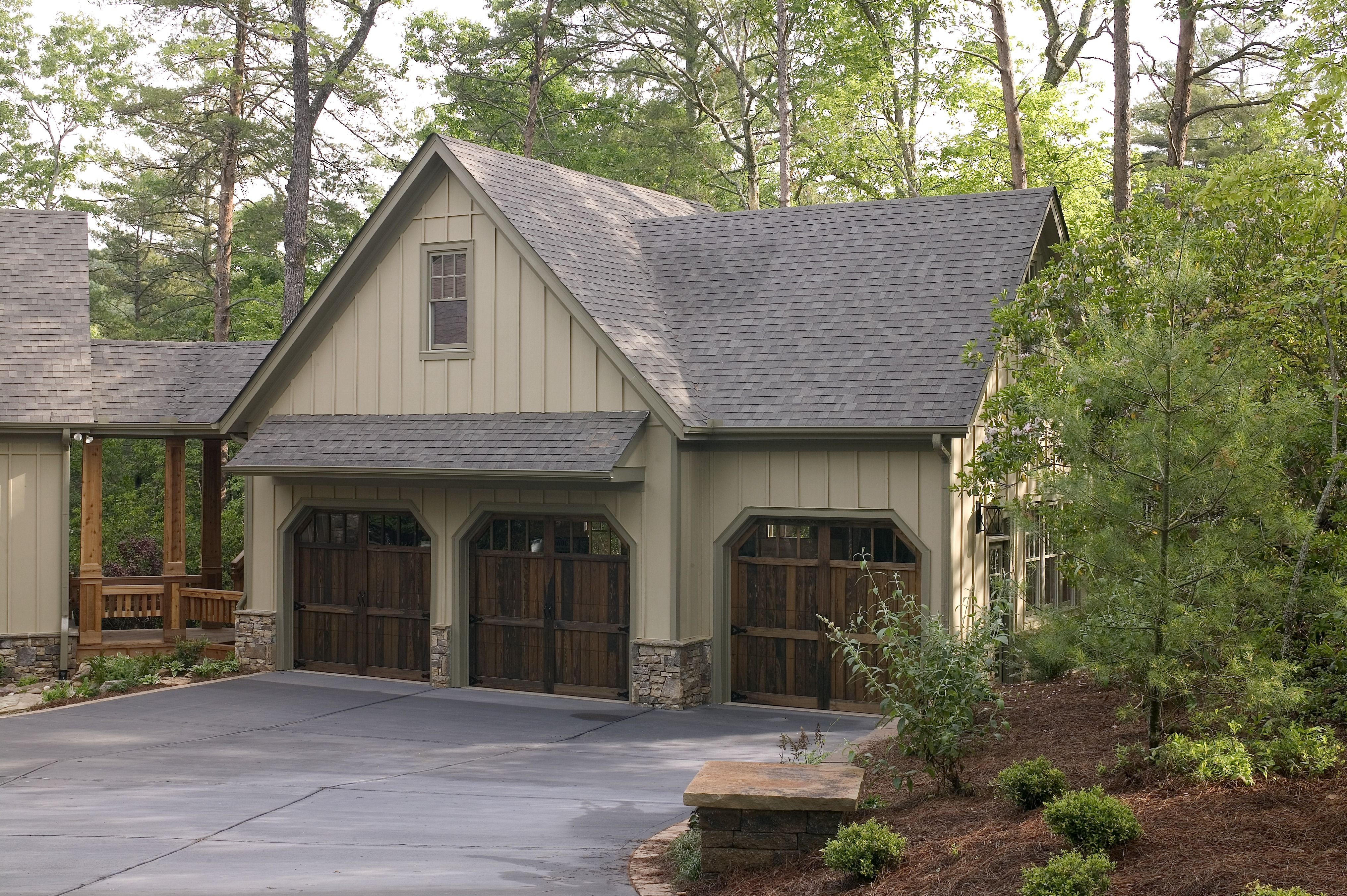 A Warm And Inviting Cape Cod Style Home With Green Siding And Beautiful Wood Garage Doors Click To See How With Images Detached Garage Cost Garage Remodel Attached Garage