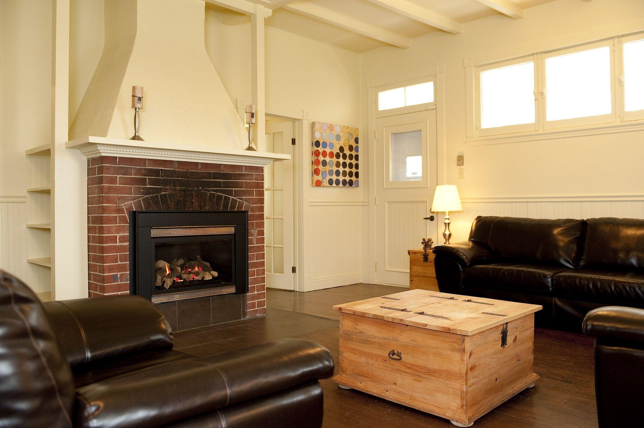 Salon avec magnifique foyer rustique.