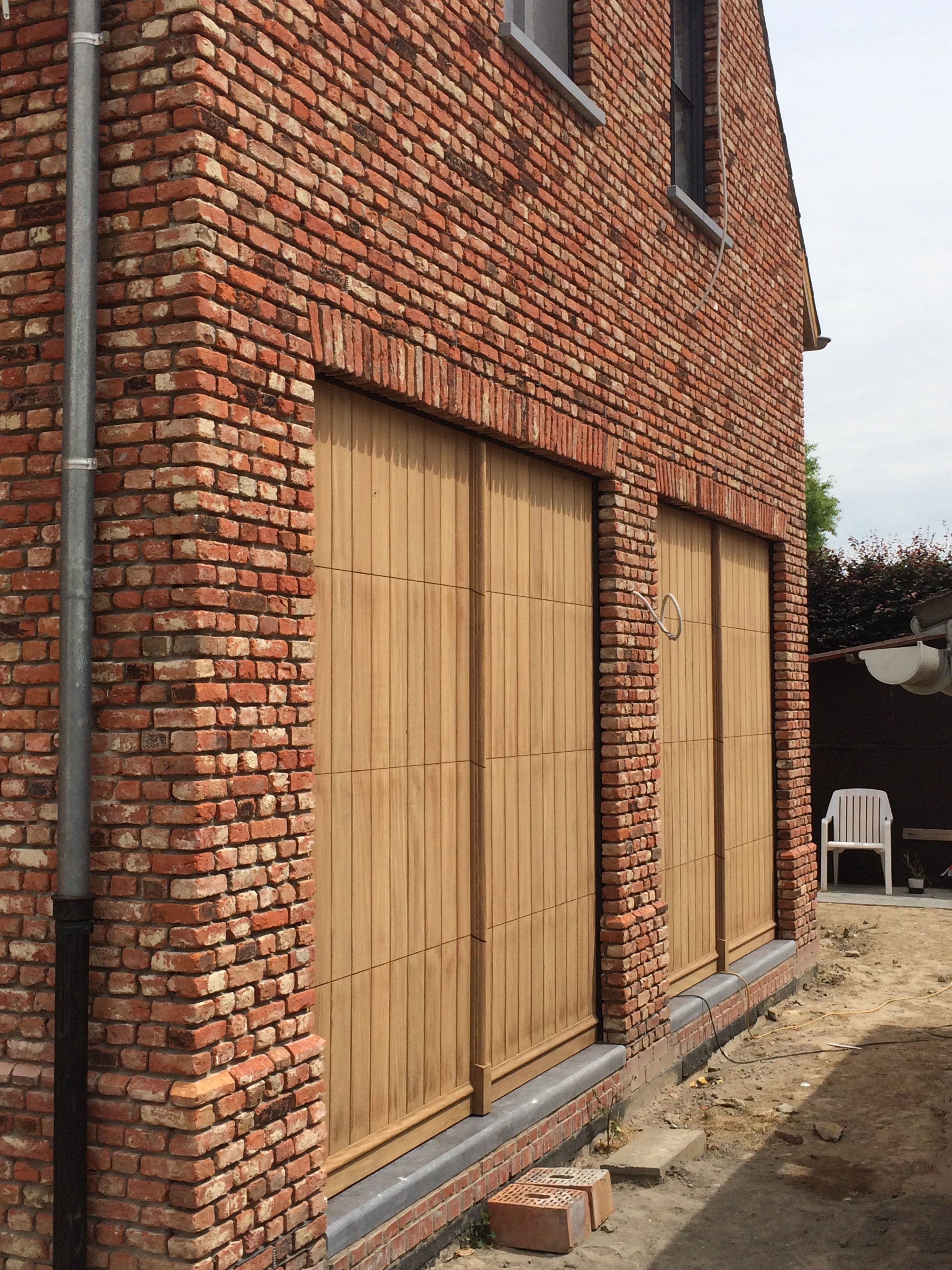 Dubbele garagepoort in hout met makelaar en plint (met