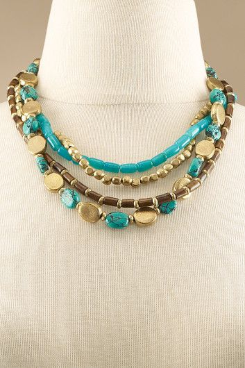 A medley of beads - golden brass, teal glass, brown bone and turquoise howlite - harmonize with Southwestern sizzle in this artisanal, multi-strand necklace.