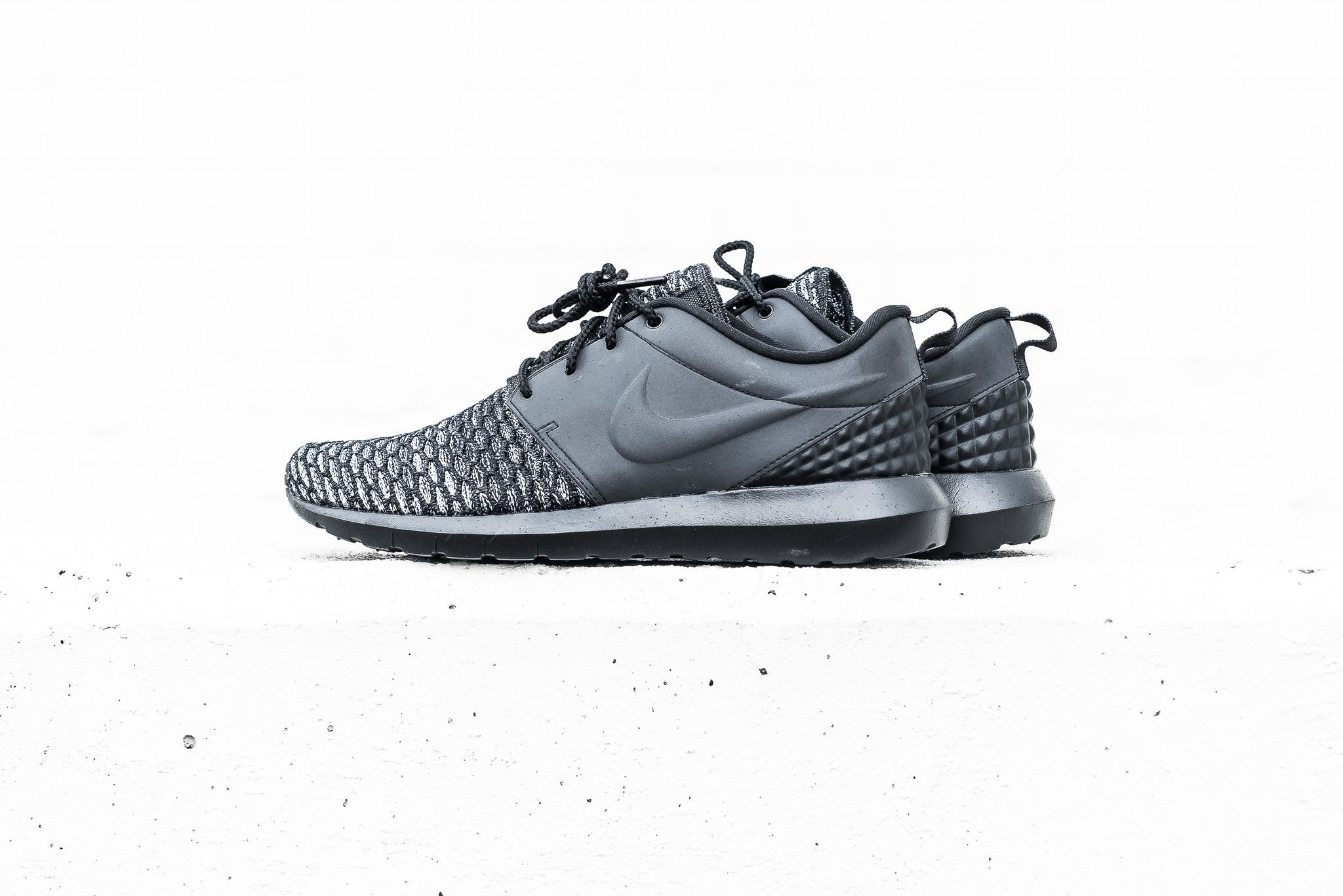 9dceab0fdd3c The NM Flyknit edition of the Nike Roshe One is receiving its latest  colorway in black with dark grey and white mixed in. The sneaker takes on a  blend of t