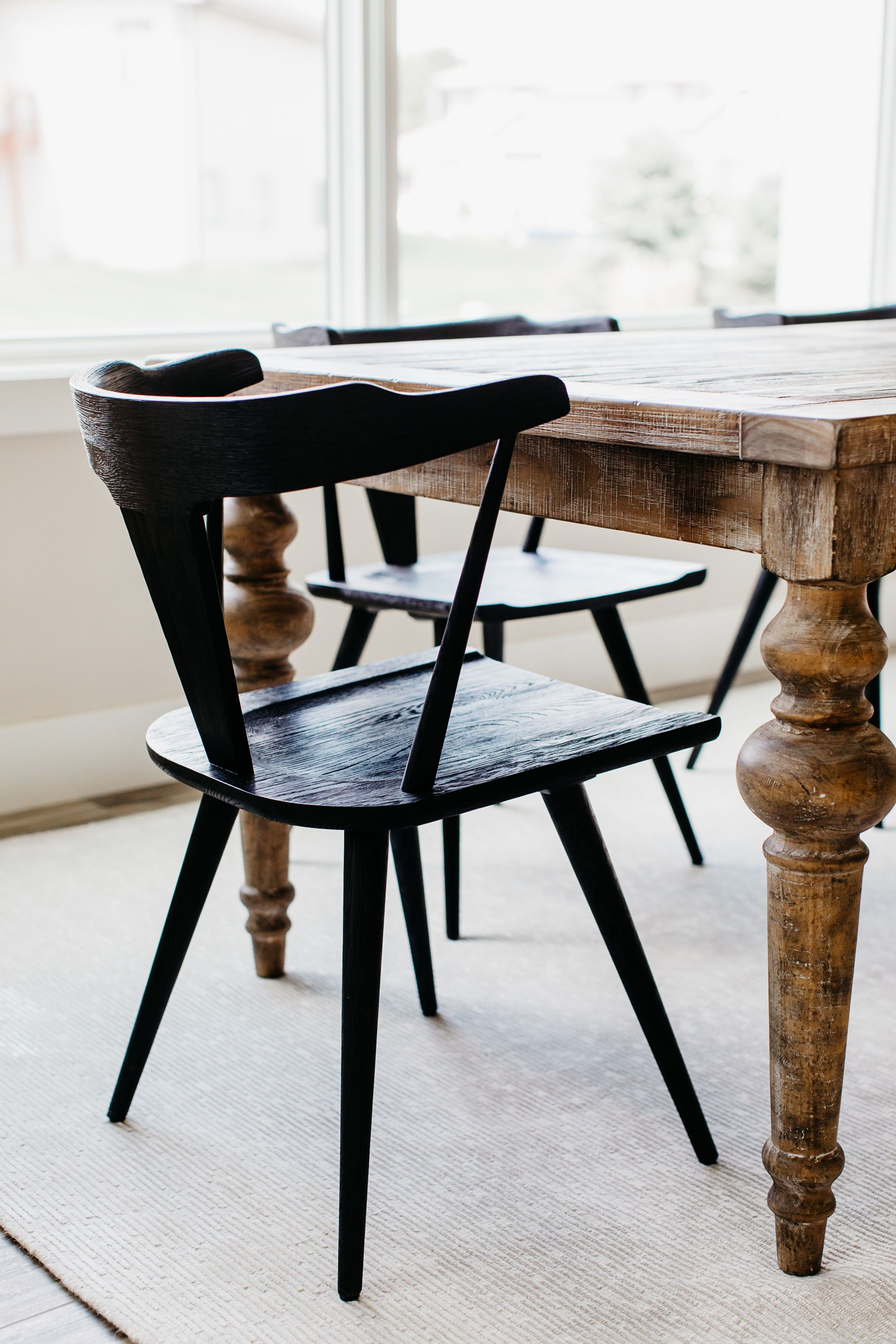 Black wishbone chairs with wooden dining table contrast