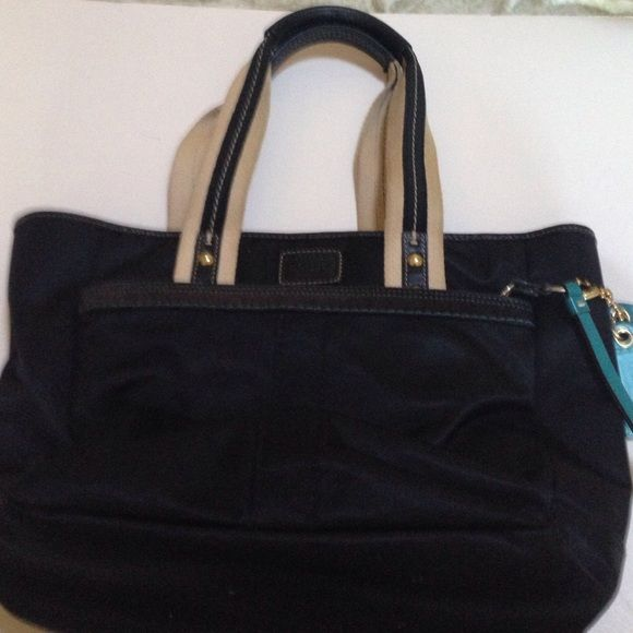 Black coach purse Black purse with teal stitching and accents. Waterproof fabric. Interior has two inter pockets and one zippered pocket. Front zippered pocket as well. Fits over the shoulder. Comes with coach storage bag. Coach Bags Shoulder Bags