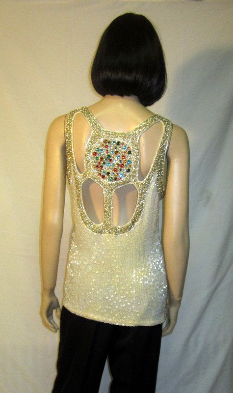 This is an exquisite 1980s, evening, sleeveless top/blouse, with a side zipper for closure, beautifully embellished with white and silver bugle beads, faux pearls, and a large jeweled medallion at its back encrusted with glass faux gemstones. The front of the top/blouse is elegantly simple, yet its back is dramatic with four cut-outs and the jeweled medallion. It is in excellent vintage condition consistent with its age and use. It measures 17 across the bust line, 16 across the wai...
